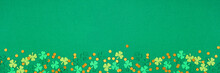St Patricks Day Green Background With Shamrock And Gold Coin Confetti Bottom Border. Top View Banner With Copy Space.