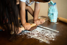 Brother And Sister Preparing Chocolate Cookies Together. Teamwork To Roll Out The Dough With The Rolling Pin.