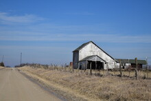 Old Barn In A Field By A Gravel Road