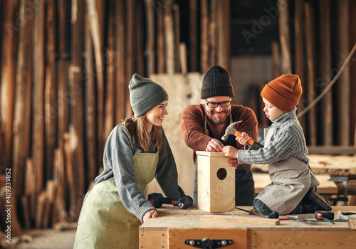 Canvas Print Kid with parents assembling wooden bird house in craft workshop