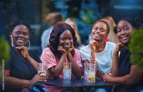 a group of beautiful happy african american women, girls chilling out at summer outdoor cafe, drinking cocktails and having fun - fototapety na wymiar