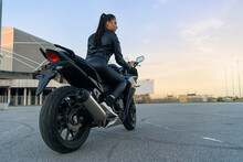 Back View Of Beautiful Young Woman In Black Leather Jacket And Pants On Outdoors Parking Rides On Stylish Sports Motorcycle At Sunset.