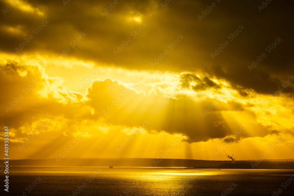 Fototapeta A dramatic sunset through the clouds over the ocean with rays of light piercing the clouds.