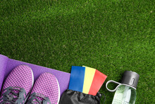 Flat Lay Composition With Fitness Elastic Bands On Green Grass. Space For Text
