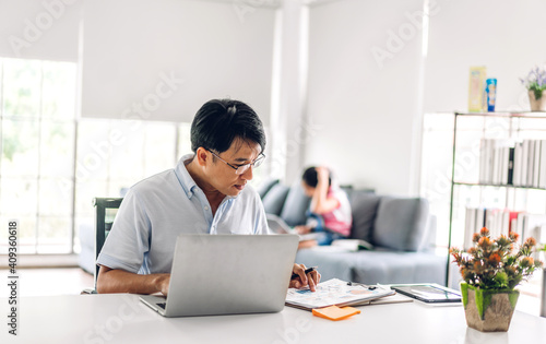 Canvas Smiling asian man relaxing using laptop computer working and video conference meeting chat with his girl daughter learning reading book and studying knowledge at home