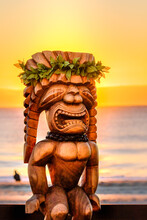 Hawaiian Tiki Statue With An Amazing Sunrise In The Background. The Tiki Is Dressed Up With Traditional Leaves And A Macadamia Necklace. It Is Made Of Wood And Looks Large In Size.