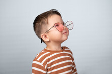 Cute Toddler Baby Boy Wearing Pink Sunglasses. Young Guy Boy In A Striped Sweater Posing On A Gray Background, Smiles And Looks To The Side , Closeup.