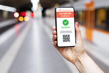 Person In Train Station Holding Mobile Phone Showing Valid Digital Vaccination Certificate