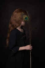 Classic Dark Renaissance Portrait En Profile Of A Redheaded Girl With A Peacock Feather In Front Of Her Eye