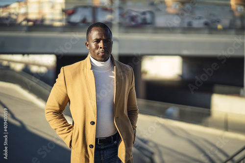 Fototapety, obrazy: Closeup shot of a stylish handsome African male in a coat going up the stairs