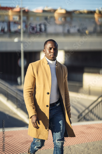 Fototapety, obrazy: Vertical shot of a stylish handsome African male in a coat going up the stairs