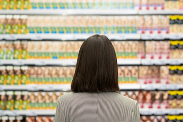 Back view of female consumer standing by large shelf with cosmetic products