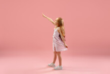 Pointing, Happy. Childhood And Dream About Big And Famous Future. Pretty Longhair Girl On Coral Pink Studio Background. Childhood, Dreams, Imagination, Education, Facial Expression, Emotions Concept.