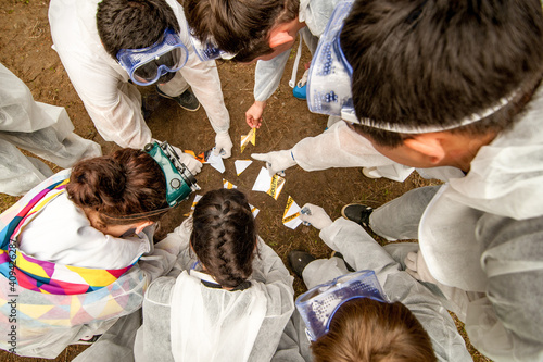Photo Top view of students in white robes doing research project in a forest with scie