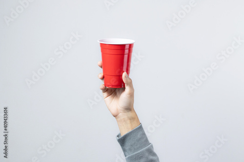 Hand raising the red cup, Copy space. © Maxky