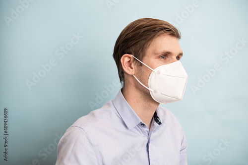 Fotografia, Obraz Man wearing FFP2 and KN95 face mask while standing against blue background