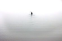High Key Image Of A Silhouette Of A Man Rowing A Canoe. Minimalist Photography Concept