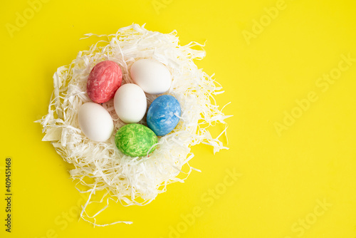 Many different colors painted eggs on nest of white paper straw Fototapeta