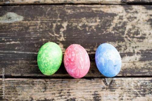 Valokuvatapetti Three easter colored eggs on wood background