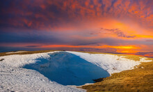 Grass Hill With Melting Snow At The Sunset, Spring Outdoor Evening Scene