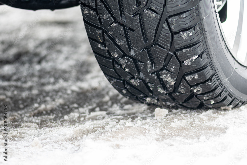 Fototapeta Close up winter tire of a car on the road covered by snow and ice driving in extreme cold temperature