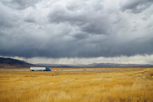 A Semi Truck Travelling On A Rural Highway With Yellow Tall Grass And Dark Storm Clouds