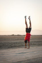 Young Sporty Man Exercising Outdoors Doing Gymnasitcs Training And Headstand