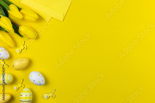 Beautiful yellow tulips with colorful easter eggs, bunnies and envelope on yellow background Wallpaper Mural