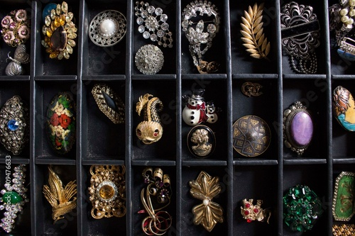 Billede på lærred A lot of differents broochs and pins displayed inside a black box
