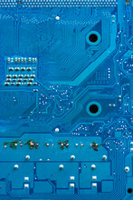 The Reverse Side Of The Microboard On A Blue Background. Electronic Board With Electrical Components, Computer Equipment.