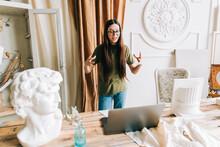 Young Caucasian Woman In Eyeglasses Video Calling In App Virtual Chat Using Laptop In Home Art Studio.