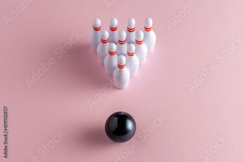 Tableau sur Toile Bowling ball and white skittles on pastel pink background