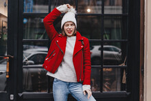 Lovely Girl In Red Coat And Jeans Is Having Fun, Winking, Showing Her Tongue And Holding Knitted Hat Pompom Against Window