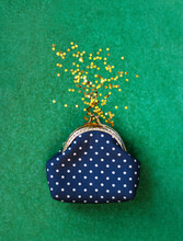 Glitter Confetti Golden Stars Crumble Out Of Polka Dot Purse On Green Background