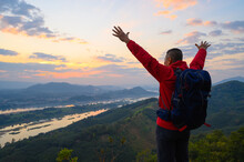 Senior Man Standing The Cliff Open Arms Enjoying The View Of Mekong River At Sunrise At Phu Pha Dak In Nong Khai, Thailand