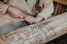 The Hands Of The Man Carving The Traditional Scandinavian Pattern On The Tree. Old Traditional Crafts. Color Close-up Photo.
