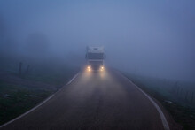 Truck Driving At Night On A Narrow Road With Poor Visibility Due To Fog.