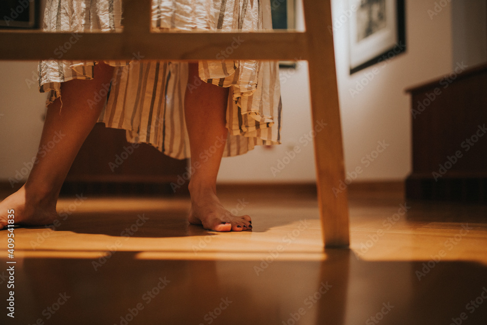 Fototapeta Closeup shot of female feet who is wearing a long dress and standing on the floor