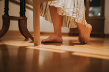 Closeup Shot Of Female Feet Who Is Wearing A Long Dress And Standing On The Floor