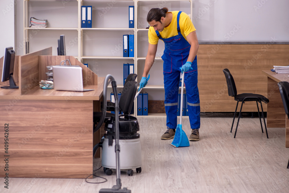 Fototapeta Young male contractor cleaning the office
