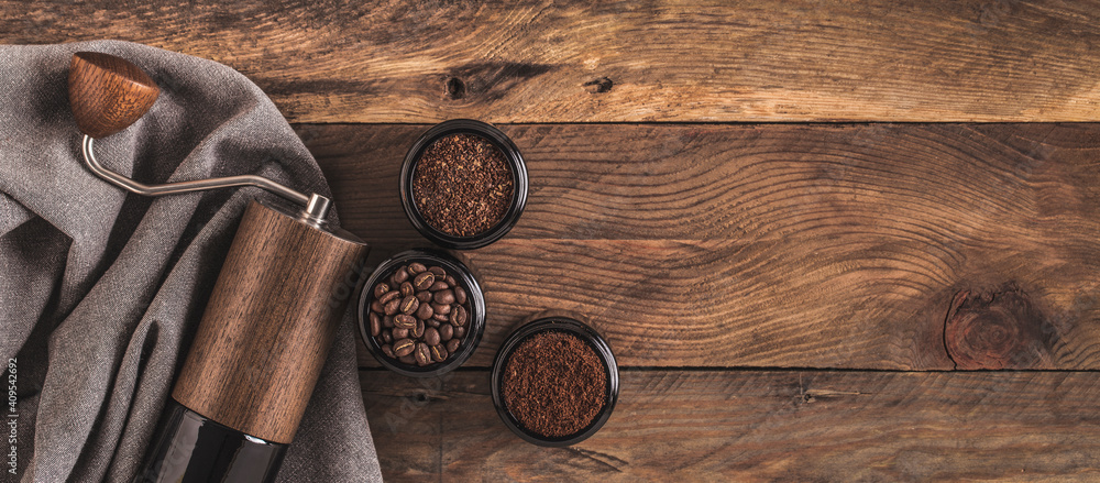 Fototapeta Manual Coffee grinder and jars of fresh ground coffee from roasted beans on wooden rustic table. Banner.