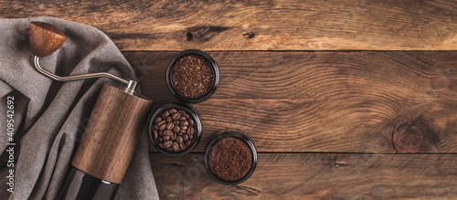 Foto Manual Coffee grinder and jars of fresh ground coffee from roasted beans on wooden rustic table