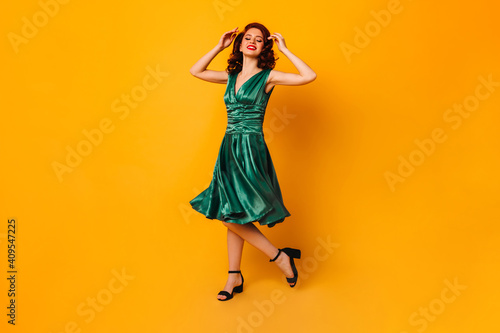 Obraz Enthusiastic ginger woman dancing on yellow background. Full length view of stunning young lady in green dress. - fototapety do salonu