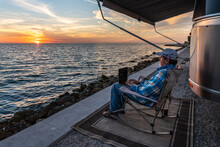 A Man, Person Sitting On A Chair By The Ocean Watching The Sunset While Working On His Laptop Computer Remotely, Sunshine Skyway, Tampa Bay, Florida