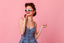 Magnificent Pinup Girl Posing In Sunglasses. Studio Shot Of Dreamy Ginger Woman Isolated On Pink Background.