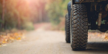 Part Of An Off-road Vehicle On A Rugged Road In The Forest . Travel Concept With Sunset And Mountains. Close Up Photo Of Off Road Wheel. Off-road Travel On Mountain Road.