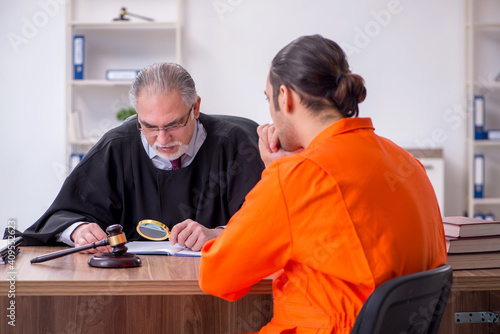 Fotomural Old male judge meeting with young captive in courthouse