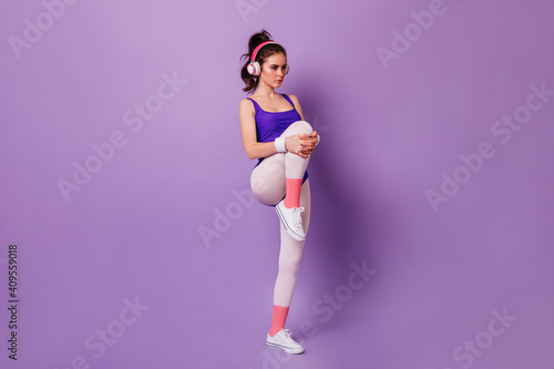 Fototapeta Woman in headphones listens to music and does warm-up before fitness workout on purple background obraz