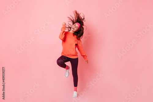 Obraz Lady in bright sweatshirt and brown leggings dances against pink background. Fitness trainer enjoying workout - fototapety do salonu