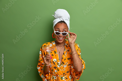 Photo of cheerful dark skinned female with healthy look wears sunglasses wrapped towel on head dressing gown holds cocktail isolated over vivid green background. Domestic party and entertainment © Wayhome Studio